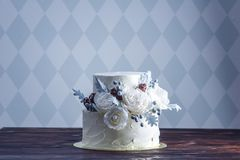 Delicate white bunk wedding cake decorated with an original design using mastic roses. Concept of festive desserts. Delicate white bunk wedding cake decorated royalty free stock photo