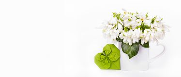 Delicate white flowers and paper heart. Snowdrops and origami heart. Copy space. stock photo