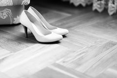 Delicate white shoes stand on the floor Stock Image