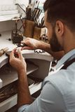 Delicate work. Close-up portrait of young male jeweler polishing silver ring at his jewelry making studio. Jewelry making workshop. Master`s hands stock photo