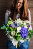 Delicate young woman with flowers bouquet Stock Image