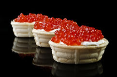 Red caviar in tartlet, isolated over black Stock Image