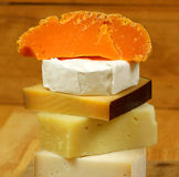 Delicatessen - cheese. Closeup of various types of cheese forming tower stock photo