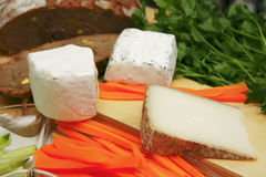 Delicatessen cheese on cut board Stock Photos