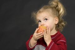 Delicious. Girl eating an apple Stock Images