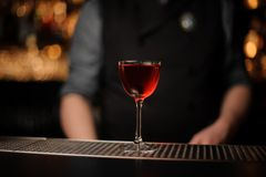 Alcohol drink with cherry with bartender behind royalty free stock photography