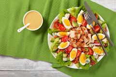 American cobb salad on a plate. Delicious american cobb salad of hard boiled egg, blue mold cheese, crispy fried bacon, romaine lettuce, grilled chicken breast royalty free stock image