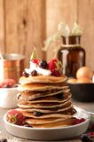 Delicious american pancakes on white plate decorated with sour cream and fresh berries stock photo