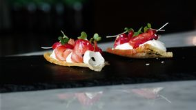 Delicious amuse bouche appetizer, cured salmon with beetroot, chess and orange blossom royalty free stock photo