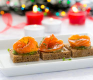 Delicious appetizer canapes of black bread with smoked salmon Stock Photography