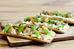 Delicious appetizer with fried mushrooms and fresh green bell pepper on a wooden board. Simple and hearty vegetarian snack Stock Photography
