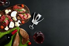 Delicious appetizer to wine - ham, cheese, baguette slices, tomatoes, served on a wooden board, and glass with red wine. On black surface. Still life royalty free stock photography