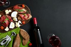 Delicious appetizer to wine - ham, cheese, baguette slices, tomatoes, served on a wooden board, and glass with red wine stock photography