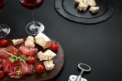 Delicious appetizer to wine - ham, cheese, baguette slices, tomatoes, served on a wooden board, and glass with red wine. On black surface. Still life stock photography