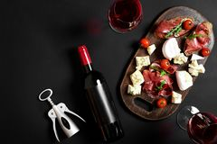 Delicious appetizer to wine - ham, cheese, baguette slices, tomatoes, served on a wooden board, and glass with red wine. On black surface. Still life royalty free stock photos