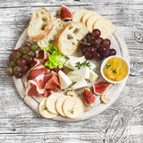 Delicious appetizer to wine - ham, cheese, grapes, crackers, figs, nuts, jam Stock Photos
