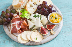 Delicious appetizer to wine - ham, cheese, grapes, crackers, figs, nuts, jam. Served on a light wooden board stock photography