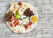 Delicious appetizer to wine - ham, cheese, grapes, crackers, figs, nuts, jam. Served on a light wooden board royalty free stock images