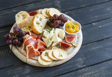 Delicious appetizer to wine - ham, cheese, grapes, crackers, figs, nuts, jam, served on a light wooden board Stock Photography