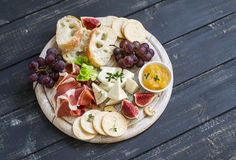Delicious appetizer to wine - ham, cheese, grapes, crackers, figs, nuts, jam, served on a light wooden board Royalty Free Stock Images