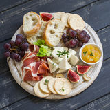Delicious appetizer to wine - ham, cheese, grapes, crackers, figs, nuts, jam, served on a light wooden board Royalty Free Stock Photos