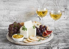 Delicious appetizer to wine - ham, cheese, grapes, crackers, figs, nuts, jam, served on a light wooden board, and two glasses with Stock Photos