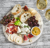 Delicious appetizer to wine - ham, cheese, grapes, crackers, figs, nuts, jam, served on a light wooden board, and two glasses with Stock Images