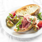 Delicious appetizer to wine - toast with ham, olives and cherry tomatoes Stock Images