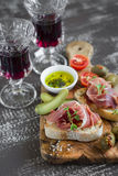 Delicious appetizer to wine - toast with ham, olives, tomatoes and red wine olive Board Stock Photos