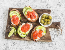 Delicious appetizers - cream cheese, smoked salmon and avocado sandwiches and olives on a wooden board. On a light background Royalty Free Stock Photography