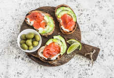 Delicious appetizers with wine - cream cheese, smoked salmon and avocado sandwiches and olives on a wooden board. Royalty Free Stock Images