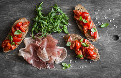 Delicious appetizers for wine or snack - cherry tomatoes bruschetta, proscutto and arugula. Mediterranean style food. On wooden ba. Ckground, top view Stock Photos