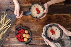 Delicious and appetizing breakfast of porridge with blueberries and fresh raspberries. Still life on a wooden background with hands Royalty Free Stock Photography