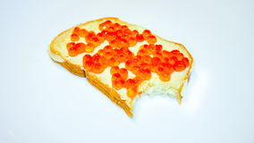 Delicious appetizing sandwich with red caviar on light background. Delicious appetizing bred peace with fish caviar without small peace cut by teath. fresh fish Royalty Free Stock Image