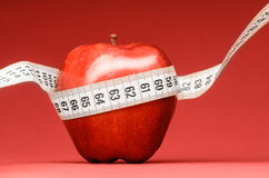Delicious apple with measuring tape Royalty Free Stock Images
