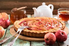 Delicious apple pie with organic red apples, honey and tea on sh. Abby blue background. Healthy apple dessert Stock Photography
