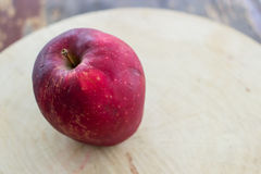 Delicious apple. Ripe red apple on a wooden background Royalty Free Stock Image