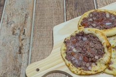 Delicious Arabic Esfiha, with fillings cheese and meat with tomato and onion. Served on a wooden board.  royalty free stock photo