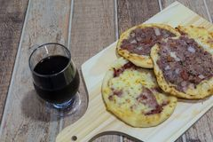 Delicious Arabic Esfiha, with fillings cheese and meat with tomato and onion. Served on a wooden board.  stock images