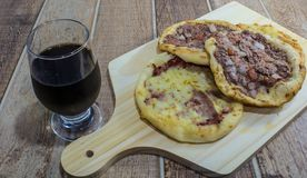 Delicious Arabic Esfiha, with fillings cheese and meat with tomato and onion. Served on a wooden board.  royalty free stock images