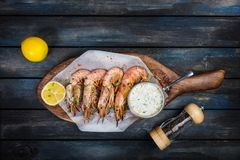 Delicious Argentine shrimp or langoustine with white sauce pepper-pot and half a lemon on a wooden board. Top view.  Stock Photo