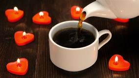 Delicious aromatic coffee at the breakfast for a loved one. Small cup of of white color, on the brown wooden table lit candles in the shape of heart, slow stock video