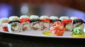 Delicious asian restaurant dish - sushi rolls with wasabi ginger red and black caviar stock video footage