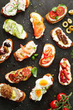 Delicious assortment of different canapes. Topped with egg, tomato, prawns, salmon, chorizo, radish, cucumber and olives on quark or cream cheese and crusty stock images