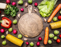 Delicious assortment of farm fresh various vegetables  lined frame with a chopping board in the middle on wooden rustic background Stock Photography