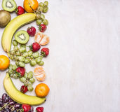 Delicious assortment of fresh fruit  laid out in a border on a white rustic background top view Superfoods health or detox die Stock Photos