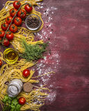 Delicious assortment of ingredients for cooking pasta with tomatoes, flour, butter, black pepper, herbs salt on wooden rustic Royalty Free Stock Photography