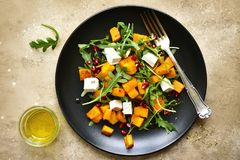 Delicious autumn pumpkin salad with arugula, feta cheese and pom. Egranate seeds on a black plate over beige slate, stone or concrete background.Top view royalty free stock photography