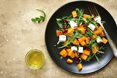 Delicious autumn pumpkin salad with arugula, feta cheese and pom. Egranate seeds on a black plate over beige slate, stone or concrete background.Top view with royalty free stock photos