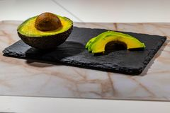 Avocado prepared for sushi with pizarre table royalty free stock image